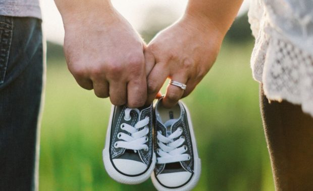 a couple holding hands and baby shoes after using parenting wisely